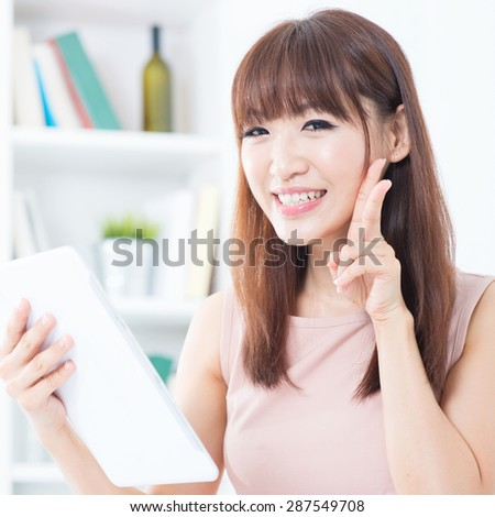 Portrait of attractive Asian girl using digital tablet and showing v hand sign. Young woman indoors living lifestyle at home. - stock photo