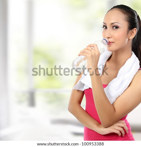 portrait of attractive asian smiling woman drinking water - stock photo