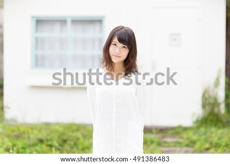 portrait of attractive asian woman standing in front of house
