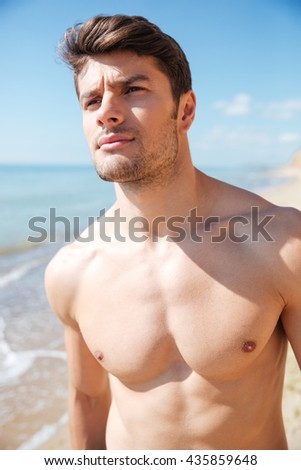 Portrait of attractive athletic young man on the beach - stock photo