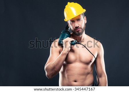 Portrait of attractive bearded workman shirtless, with drill yellow helmet, shirtless, standing on a gray background