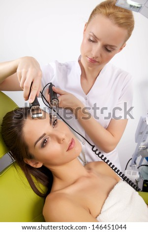 Portrait of attractive beautiful young adult brunette woman having a stimulating facial treatment from a therapist on the table in professional clinic spa