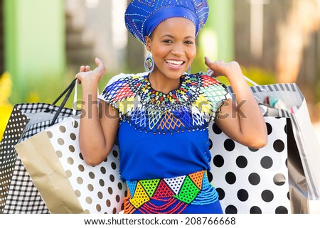 portrait of attractive black woman carrying shopping bags - stock photo