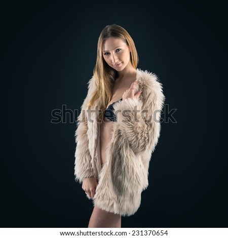 Portrait of attractive blond woman with fur against black background. - stock photo