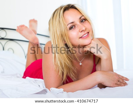 Portrait of attractive blonde girl in red lingerie lying on the bed
