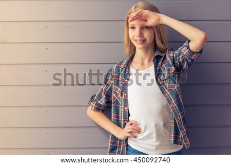 Portrait of attractive blonde teenage girl in casual clothes posing,  looking away and smiling, standing against gray wall - stock photo