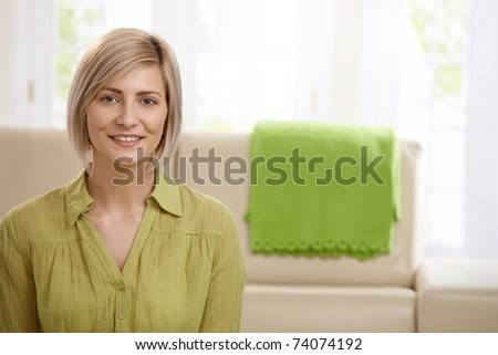 Portrait of attractive blonde woman smiling at home, sofa in background. - stock photo