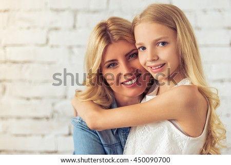 Portrait of attractive blondes, teenage girl and her mother, hugging, looking at camera and smiling, against white brick wall