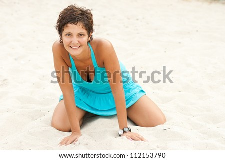 portrait of attractive brunet woman in blue sitting on a sand