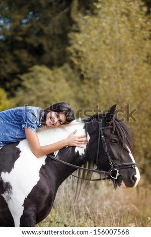 portrait of attractive brunette female rider embracing her horse and looking at camera - stock photo