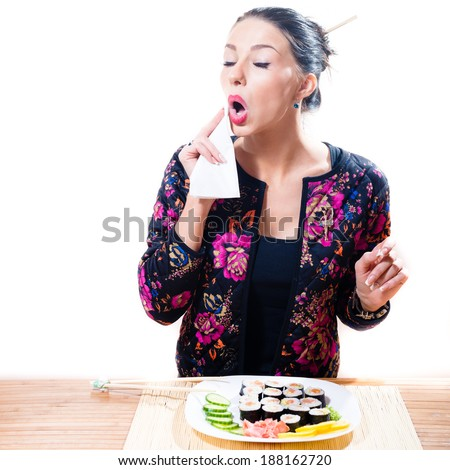 portrait of attractive brunette girl wiping her mouth with a napkin isolated on a white background - stock photo