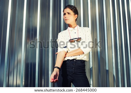 Portrait of attractive brunette hipster woman posing on shiny wall background, fashionable model standing on silver background looking away, filtered image - stock photo