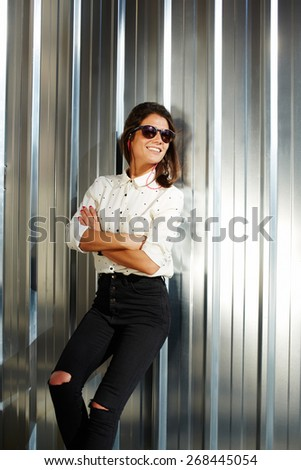 Portrait of attractive brunette hipster woman posing on shiny wall background in sunglasses, smiling fashionable model standing on silver background with crossed arms - stock photo