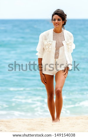 Portrait of attractive brunette in elegant white clothes walking on sandy beach. - stock photo