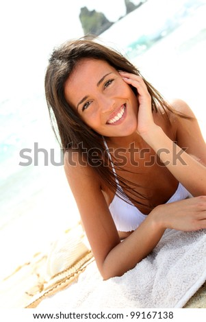 Portrait of attractive brunette laying on a beach - stock photo