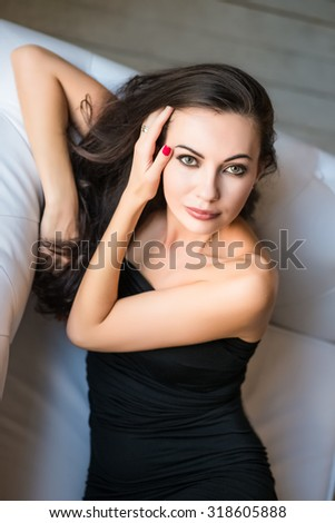 Portrait of attractive brunette posing on the couch - stock photo