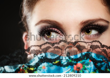 Portrait of attractive brunette woman. Closeup of face of spanish girl flamenco dancer hidden behind fan. - stock photo