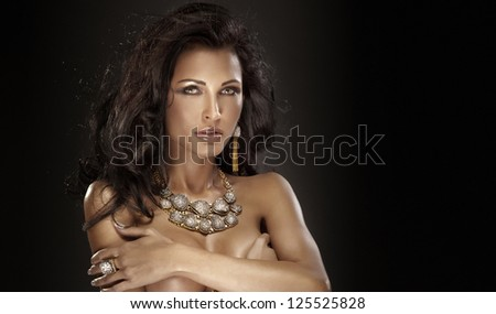 Portrait of attractive brunette woman wearing amazing gold jewelry - stock photo