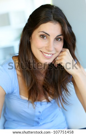 Portrait of attractive brunette woman with hand on chin - stock photo