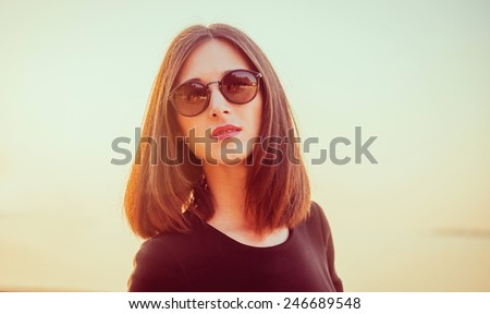 Portrait of attractive brunette woman with long hair in sunglasses on background of sea at sunny day. Image with sunlight effect - stock photo