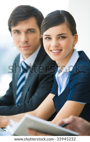 Portrait of attractive business lady looking at camera with smile on background of serious man