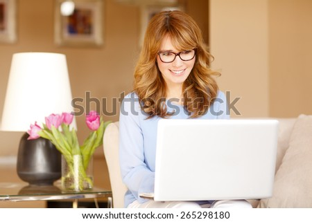 Portrait of attractive business woman sitting at sofa and working at laptop online.  - stock photo