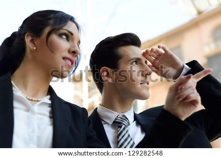 Portrait of attractive businessman and businesswoman looking at something interesting. Couple working. - stock photo