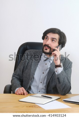 portrait of attractive businessman speaking on his mobile at his desk in the office; business concept - stock photo