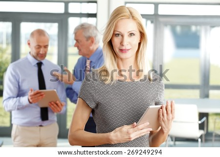 Portrait of attractive businesswoman holding digital tablet and standing at office. Sales man consulting at background. Group of business people.