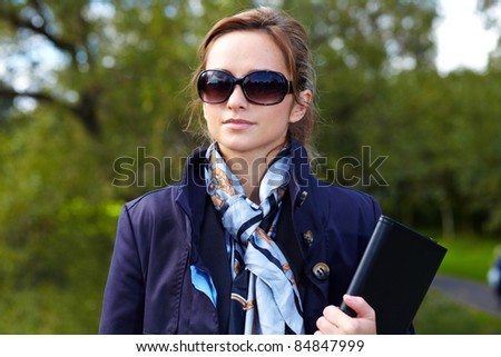 Portrait of attractive businesswoman in park, outdoor shoot with blurred background