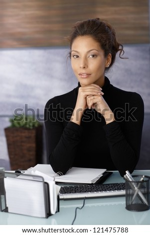 Portrait of attractive businesswoman sitting at desk in office.