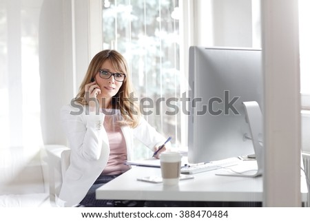 Portrait of attractive businesswoman talking on mobile phone while sitting at her workplace and making some paperwork. - stock photo