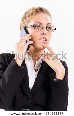 Portrait of attractive businesswoman using a mobile phone. She is thinking.