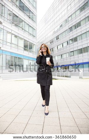 Portrait of attractive businesswoman walking on the street and using her mobile phone after business meeting.