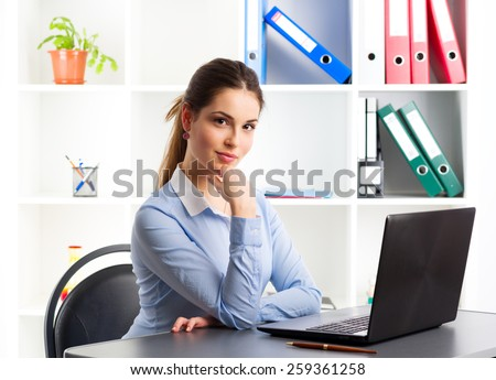 Portrait of attractive businesswoman working at computer in the office. Young successful female entrepreneur posing with laptop at her workplace.   - stock photo