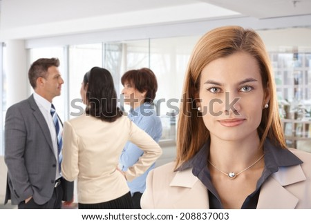 Portrait of attractive caucasian businesswoman with colleagues at office.