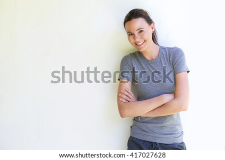 Portrait of attractive caucasian female standing with her arms crossed against white wall - stock photo