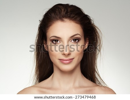 Portrait of attractive Caucasian female with wet hair looking at camera. Young lovely woman with professional makeup posing in studio. - stock photo