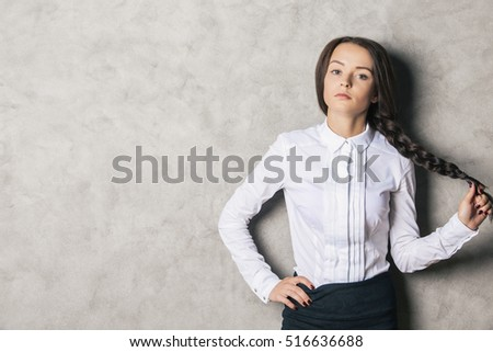 Portrait of attractive caucasian girl on textured concrete wall background with copy space