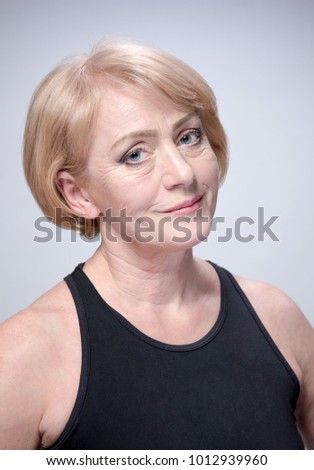 portrait of attractive  caucasian smiling mature woman blond on gray background studio shot face skin looking at camera