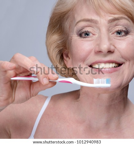 portrait of attractive caucasian smiling mature woman brushing teeth blond on gray background studio shot looking at camera