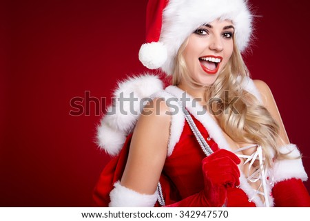 portrait of attractive caucasian smiling woman blond isolated on red studio shot in santa's hat and dress
