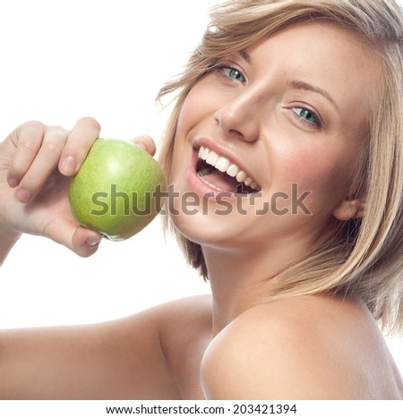 portrait of attractive  caucasian smiling woman blond isolated on white studio shot eating green apple - stock photo