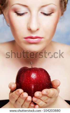 portrait of attractive caucasian smiling woman eating red apple