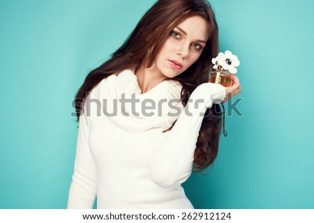 portrait of attractive caucasian smiling woman holding bottle of perfume - stock photo