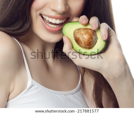 portrait of attractive  caucasian smiling woman isolated on white studio shot eating avocado