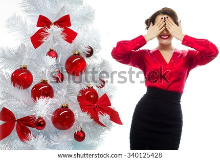 portrait of attractive  caucasian smiling woman isolated on white studio shot eyes closed by hands secret surprise christmas new year tree - stock photo