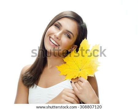 portrait of attractive  caucasian smiling woman isolated on white studio shot with yellow maple autumn leaf - stock photo