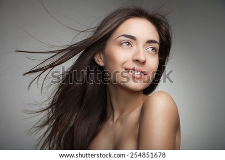 Portrait of attractive caucasian smiling woman with long hair on grey background