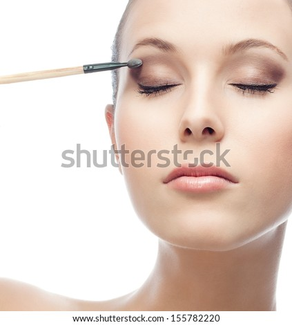 portrait of attractive  caucasian  woman applying eye shadows  isolated on white studio shot eyes closed